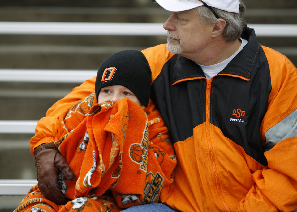 Photo - OSU alumnus Gordon Law and his son Nick Law try to stay warm before the Heart of Dallas Bowl football game between Oklahoma State University and Purdue University at the Cotton Bowl in Dallas, Tuesday, Jan. 1, 2013. Photo by Bryan Terry, The Oklahoman