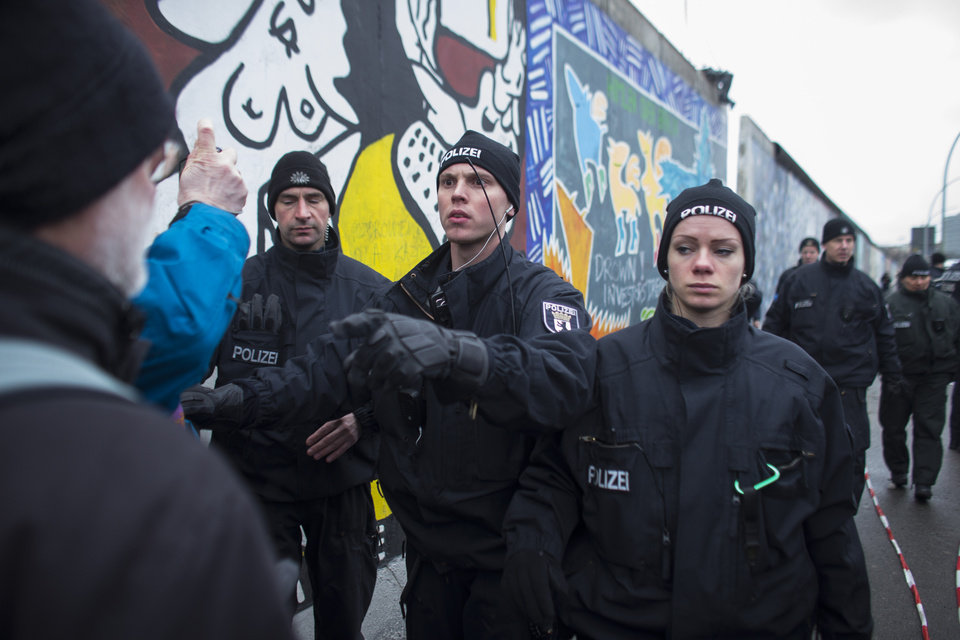 Photo - A German police officers reacts to protestors as they protect a part of the former Berlin Wall in Berlin, Germany, Friday, March 1, 2013. Construction crews stopped work Friday on removing a small section from one of the few remaining stretches of the Berlin Wall to make way for a condo project after hundreds of protesters blocked their path.(AP Photo/Markus Schreiber/Pool)