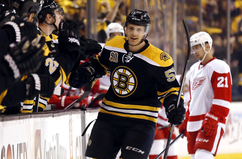 Photo - Boston Bruins' Justin Florek is congratulated at the bench after scoring a goal as Detroit Red Wings' Tomas Tatar (21) skates to the bench during the first period of Game 2 of a first-round NHL hockey playoff series in Boston Sunday, April 20, 2014. (AP Photo/Winslow Townson)