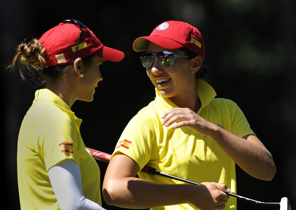 Photo - Carlotta Ciganda, right, and Azahara Monoz, laugh before playing the second hole during the second round of the International Crown golf tournament Friday, July 25, 2014, in Owings Mills, Md.(AP Photo/Gail Burton)