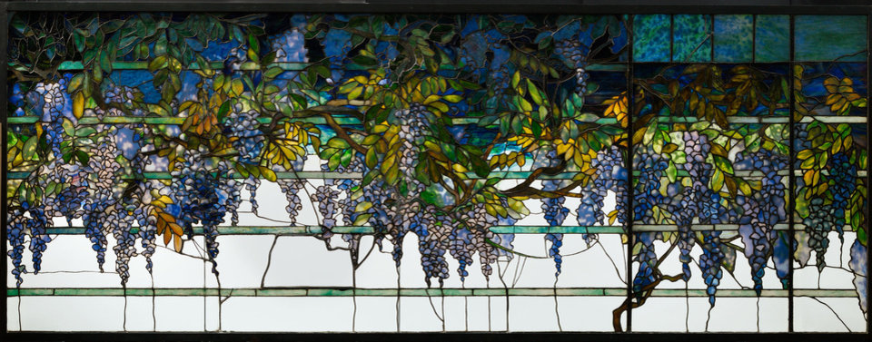 Echoes of nature: The transoms on the south side of the dining room were leaded glass windows depicting wisteria falling over the eaves. The glass panels echoed the live wisteria that grew just beyond the window. Photo courtesy Morse Museum.   <strong></strong>