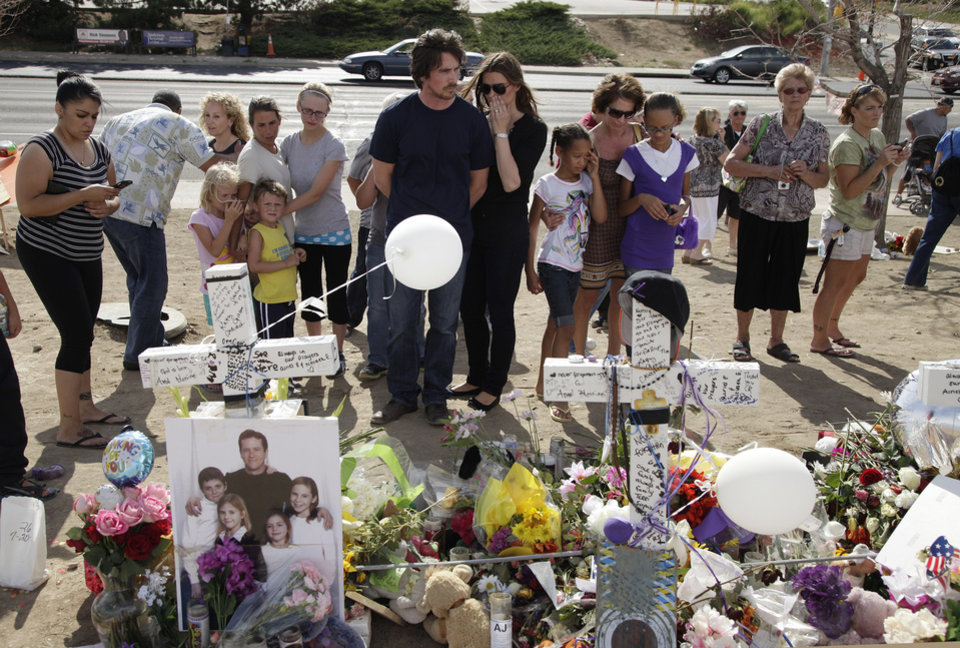 "Actor Christian Bale, center, left, and his wife Sibi Blazic visit a memorial to the victims of Friday's mass shooting, Tuesday, July 24, 2012, in Aurora, Colo. Twelve people were killed when a gunman opened fire during a late-night showing of the movie ""The Dark Knight Rises,"" which stars Bale as Batman. (AP Photo/Ted S. Warren)"