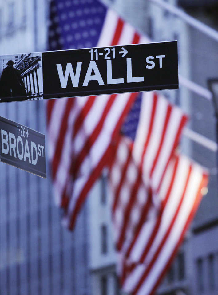 Photo - FILE - In this Aug. 9, 2011 file photo, American flags hang behind a Wall Street sign outside the New York Stock Exchange, in New York. World stock markets were mostly weaker Friday, May 30, 2014, after a government report showed the U.S. economy shrank in the first quarter and the U.S. dollar lost value against major Asian currencies. (AP Photo/Mark Lennihan, File)