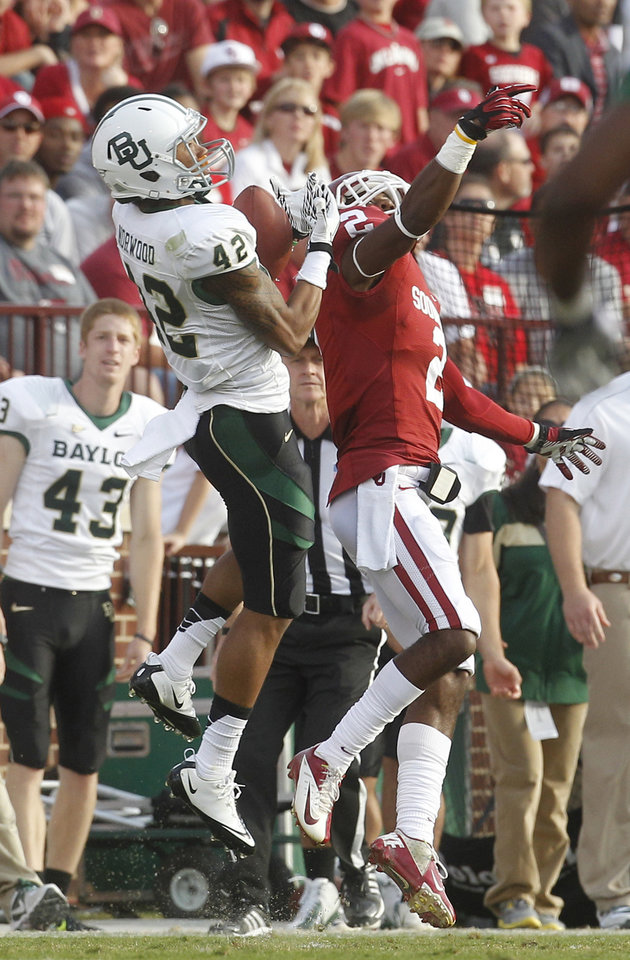 Photo -   Baylor receiver Levi Norwood (42) catches a pass in front of Oklahoma defensive back Julian Wilson (2) in the second quarter of an NCAA college football game in Norman, Okla., Saturday, Nov. 10, 2012. (AP Photo/Sue Ogrocki)