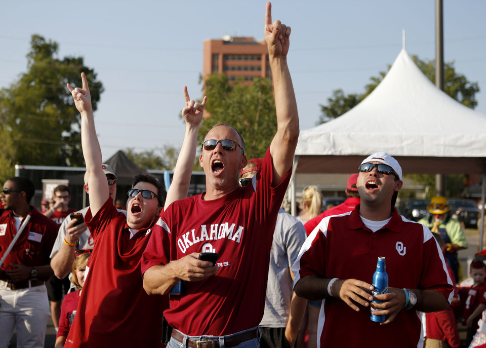 Photo - Travis Paiva, left, of Tulsa, John Elder, of Muskogee, and Casey Riggs of Tulsa cheer during Fan Fest outside the stadium prior to the college football game between the University of Oklahoma Sooners (OU) and the Kansas State University Wildcats (KSU) at Gaylord Family-Oklahoma Memorial Stadium, Saturday, September 22, 2012. Photo by Bryan Terry, The Oklahoman