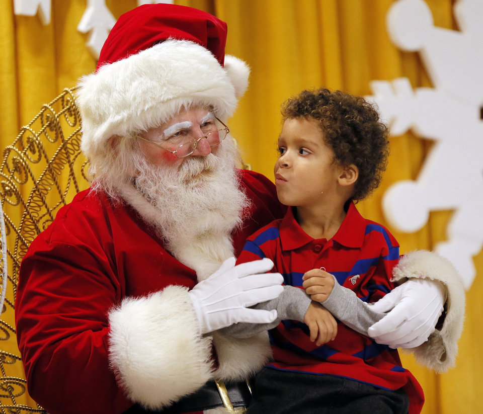 Photo - Jordan Price, 5, talks to Santa Claus during the lighting ceremony.