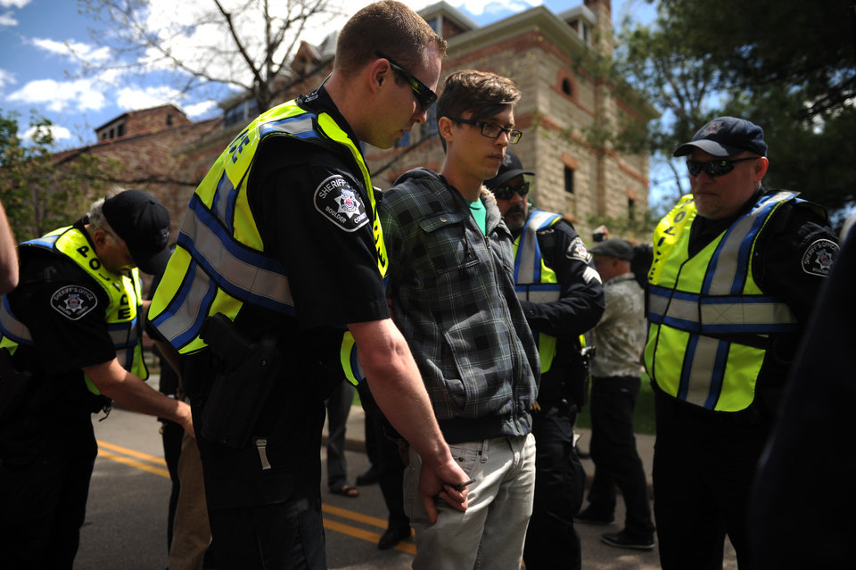Photo -   Colorado University Senior Jonathan Edwards is patted down for transportation after being arrested for trespassing on the Norlin Quad that is closed to crackdown on pro-marijuana protesters on 4-20-12 at the school in Boulder, Colorado, Friday, April 20, 2012. A block-long line of protesters marched onto the University of Colorado, testing the school's determination to push the annual April 20 marijuana celebration off campus. (AP Photo/The Denver Post, Joe Amon)