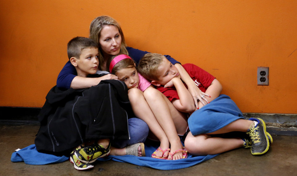 Photo - Lisa Ludlam holds her children, Jake, 6, Paige, 9, and Tony, 11, under the Cox Convention Center after fans at the Barons game were evacuated to the parking garage under the Cox Convention Center due to severe storms in Oklahoma City on Friday, May 31, 2013.  Emergency officials set out Saturday morning to see how much damage a violent burst of thunderstorms and tornadoes caused as it swept across the Midwest overnight, killing at least five and injuring dozens. The storm toppled cars and left commuters trapped on an interstate highway as it bore down during Friday's evening rush hour near Oklahoma City. The National Weather Service reported