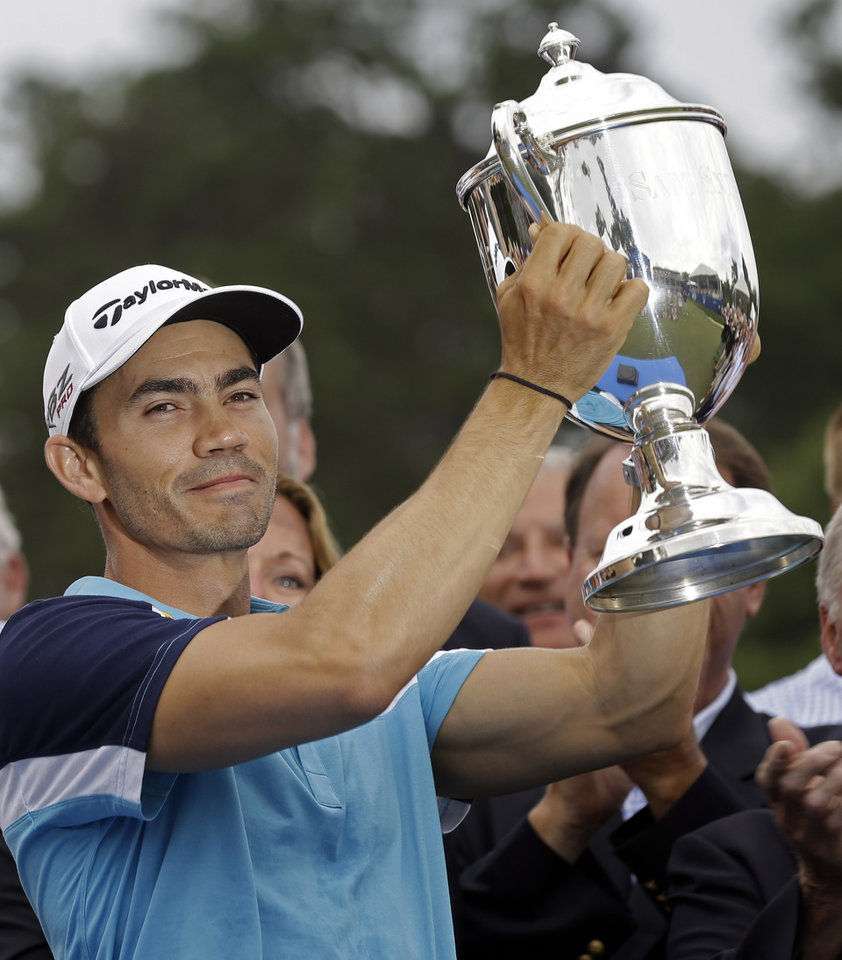 Photo - Camilo Villegas, of Colombia, holds the Sam Snead trophy on the 18th green after winning the Wyndham Championship golf tournament in Greensboro, N.C., Sunday, Aug. 17, 2014. (AP Photo/Gerry Broome)