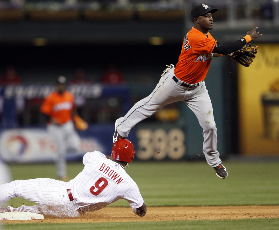 Photo - Philadelphia Phillies' Domonic Brown (9) is forced out at second as Miami Marlin's Adieny Hechavarria turns the double play by throwing out Phillies' Carlos Ruiz at first during the fifth inning of a baseball game on Friday, April 11, 2014, in Philadelphia. (AP Photo/Tom Mihalek)