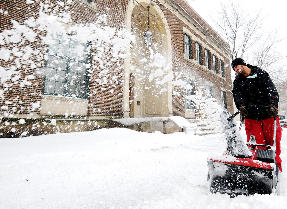 Photo - Joe Roland uses a snow blower to clear snow from the sidewalk on Thursday, Dec. 20, 2012, in downtown Winona, Minn.  The first major snowstorm of the season began its slow eastward march across the Midwest early Thursday, creating treacherous driving conditions and threatening to disrupt some of the nation's busiest airports ahead of the holiday weekend.(AP Photo/Winona Daily News, Joe Ahlquist)