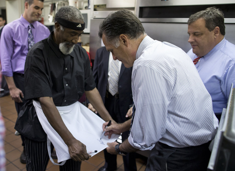 New Jersey Gov. Chris Christie accompanies Republican presidential candidate, former Massachusetts Gov. Mitt Romney as he signs the apron of an employee of Bun\'s Restaurant and Bakery during a campaign stop, Wednesday, Oct. 10, 2012, in Delaware, Ohio. (AP Photo/ Evan Vucci)