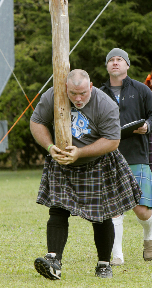 Photo - Kyle Fuller, of Arlington, Texas, competes in the caber toss during the Iron Thistle Scottish Heritage Festival.  Photo By Paul Hellstern, The Oklahoman  PAUL HELLSTERN - Oklahoman