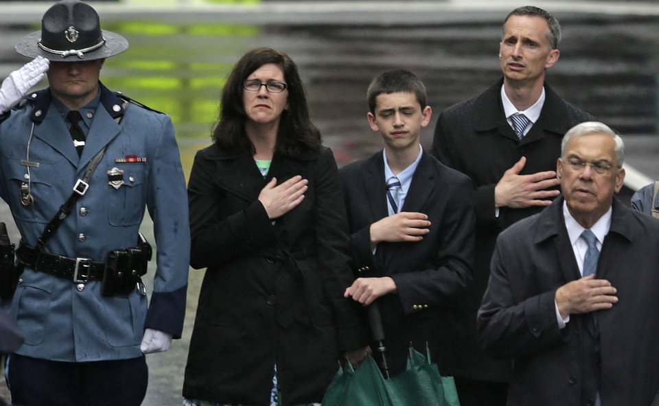 Photo - The family of 2013 Boston Marathon bombing victim Martin Richard, from left, mother Denise, brother Henry, and father Bill Richard, place their hands over their hearts as they stand with former Boston Mayor Tom Menino, right, during a tribute in honor of the one year anniversary of the Boston Marathon bombings, Tuesday, April 15, 2014 in Boston. At left is a Mass. State Trooper. (AP Photo/Charles Krupa)