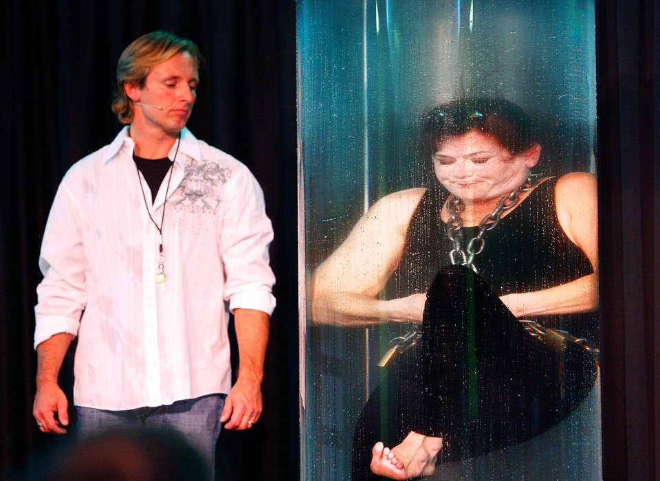Photo - Kristen Johnson escapes from leg irons and handcuffs while submerged in a water tank during a show at the Oklahoma State Fair on Saturday, Sept. 26, 2009 in Oklahoma City, Okla.  Her magician/husband/partner Kevin Ridgeway is at left.  The same escape trick was unsuccessfully attempted in January at a Thunder Basketball game.  Johnson blacked out and had to be removed from the tank by Ridgeway.  Photo by Steve Sisney, The Oklahoman. ORG XMIT: KOD