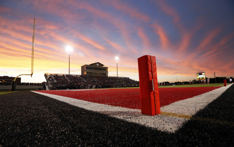 Photo - The sun sets behind the stadium during a high school football game between Norman and Yukon at Yukon High School in Yukon, Okla., Friday, Sept. 20, 2013. Photo by Nate Billings, The Oklahoman