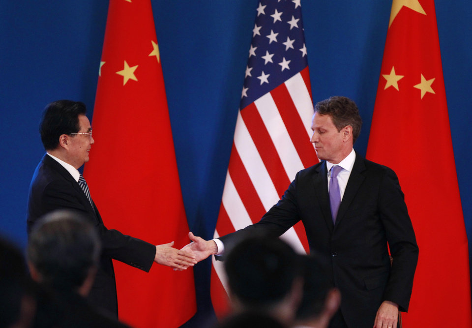 Photo -   Chinese President Hu Jintao, left, shakes hand with U.S. Treasury Secretary Timothy Geithner during the opening ceremony of the U.S.- China Strategic and Economic Dialogue at The Diaoyutai state guesthouse in Beijing, Thursday, May 3, 2012. (AP Photo/Vincent Thian)