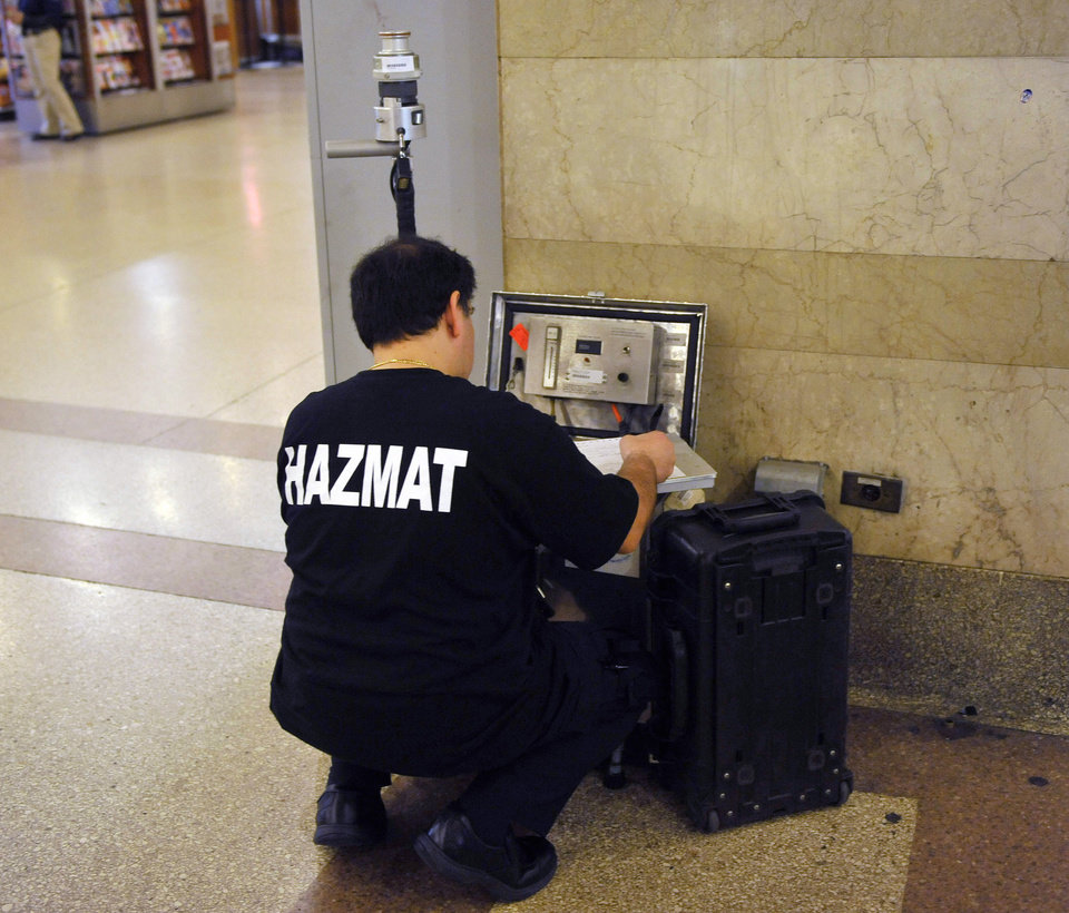 Photo - A HAZMAT officer takes readings from an air quality testing machine in Grand Central Station, Monday, May 2, 2011 in New York. Security was heightened as a result of the killing of Osama Bin Laden. (AP Photo/Stephen Chernin) ORG XMIT: NYSC103