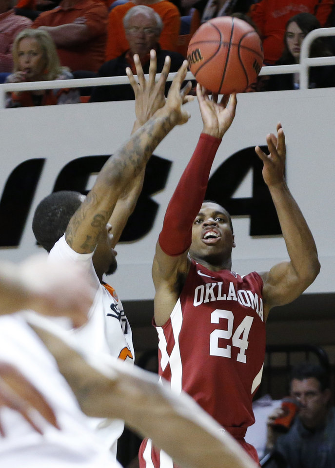 Photo - Oklahoma guard Buddy Hield (24) shoots over Oklahoma State post Kamari Murphy (21) in the first half of an NCAA college basketball game in Stillwater, Okla., Saturday, Feb. 15, 2014. Oklahoma won 77-74. (AP Photo/Sue Ogrocki)
