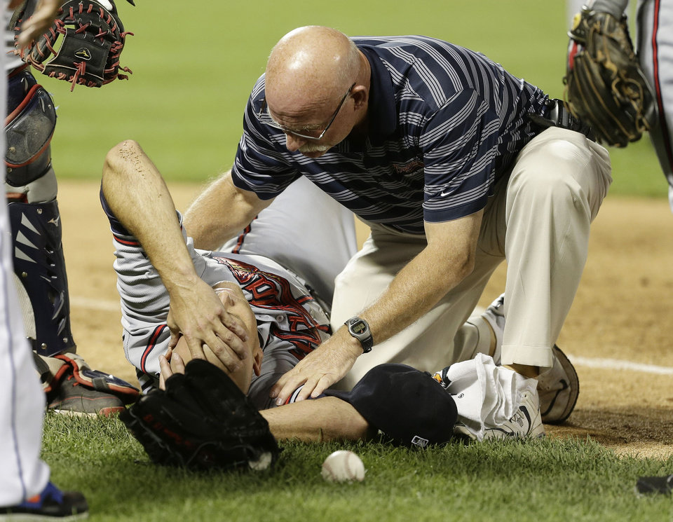 Photo - Atlanta Braves' Tim Hudson is helped by a trainer after being injured on a play at first base during the eighth inning of a baseball game against the New York Mets, Wednesday, July 24, 2013, in New York. (AP Photo/Frank Franklin II)