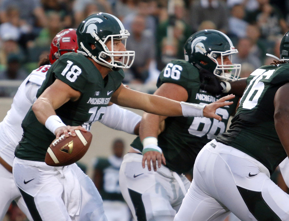 Photo - FILE - In this Aug. 29, 2014, file photo, Michigan State quarterback Connor Cook (18) scrambles against Jacksonville State during the first quarter of an NCAA college football game  in East Lansing, Mich. When No. 7 Michigan State plays at No. 3 Oregon on Saturday, the team with the old-school offense will be the unusual one. While it's become more difficult to categorize offenses these days as philosophies and schemes are blended and combined, the Spartans are among a dwindling number of teams still using what can best be described as a traditional, prostyle attack, featuring tight ends, fullbacks and the quarterback regularly taking a snap from under center. (AP Photo/Al Goldis, File)
