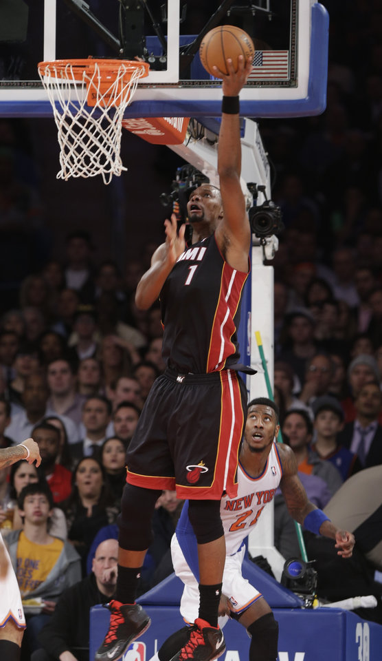 Photo - Miami Heat's Chris Bosh (1) scores in front of New York Knicks' Iman Shumpert (21) during the first half of an NBA basketball game on Thursday, Jan. 9, 2014, in New York. (AP Photo/Frank Franklin II)