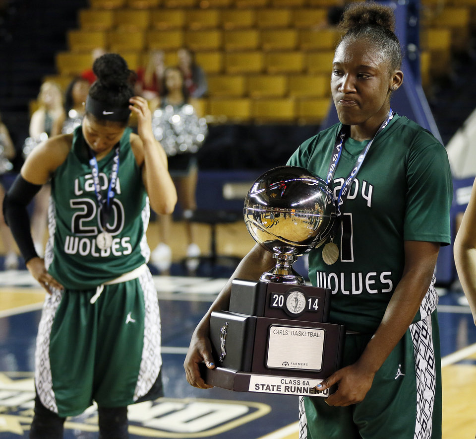 Photo - Edmond Santa Fe's Aahliyah Jackson (1) holds the runner-up trophy near Tamara Lee (20) after the Class 6A girls championship game in the state high school basketball tournament between Broken Arrow and Edmond Santa Fe at the Mabee Center in Tulsa, Okla., Saturday, March 15, 2014. Broken Arrow won, 70-51. Photo by Nate Billings, The Oklahoman