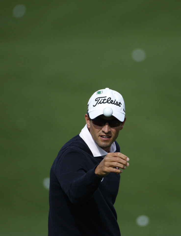 Photo - Adam Scott, of Australia, catches a golf ball from his caddie on the driving range during a practice round for the Masters golf tournament Tuesday, April 8, 2014, in Augusta, Ga. (AP Photo/Matt Slocum)