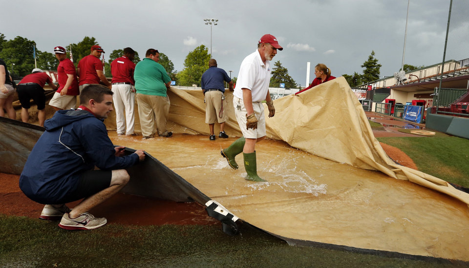 Photo - Groundskeeper Kevin Duffy and others stream standing water drain water from the infield cover during a lightning and rain delay as the University of Oklahoma Sooner (OU) softball team plays Tennessee in game two of the NCAA super regional at Marita Hynes Field on May 24, 2014 in Norman, Okla. Photo by Steve Sisney, The Oklahoman