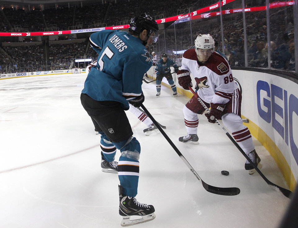 Phoenix Coyotes right wing Mikkel Boedker (89) battles for the puck against San Jose Sharks defenseman Jason Demers (5)  during the second period an NHL hockey game in San Jose, Calif., Saturday, Oct. 5, 2013. (AP Photo/Tony Avelar)