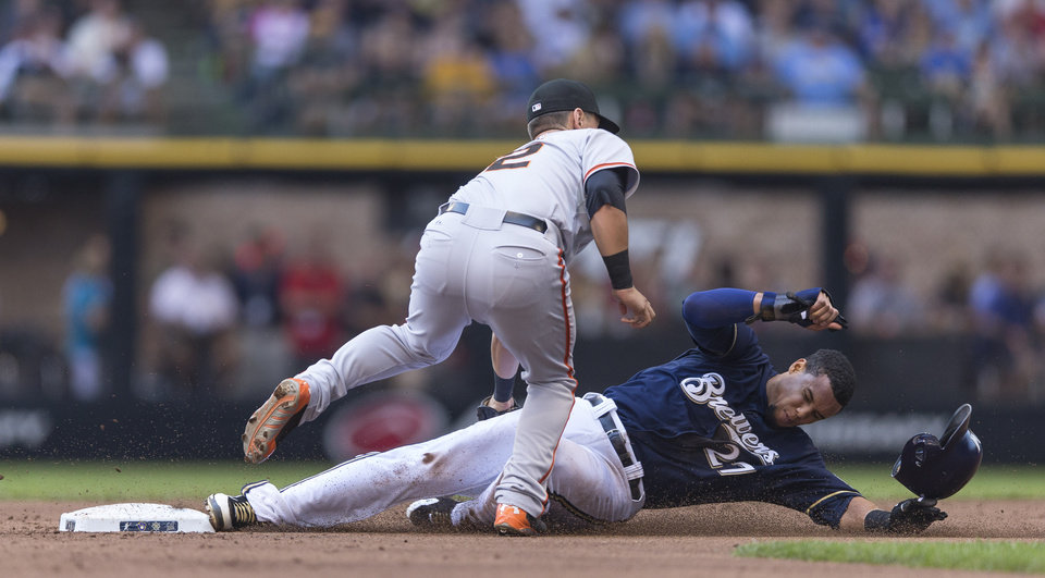 Photo - Milwaukee Brewers' Carlos Gomez is tagged out by San Francisco Giants' Joe Panik on a steal attempt during the first inning of a baseball game Thursday, Aug. 7, 2014, in Milwaukee. (AP Photo/Tom Lynn)