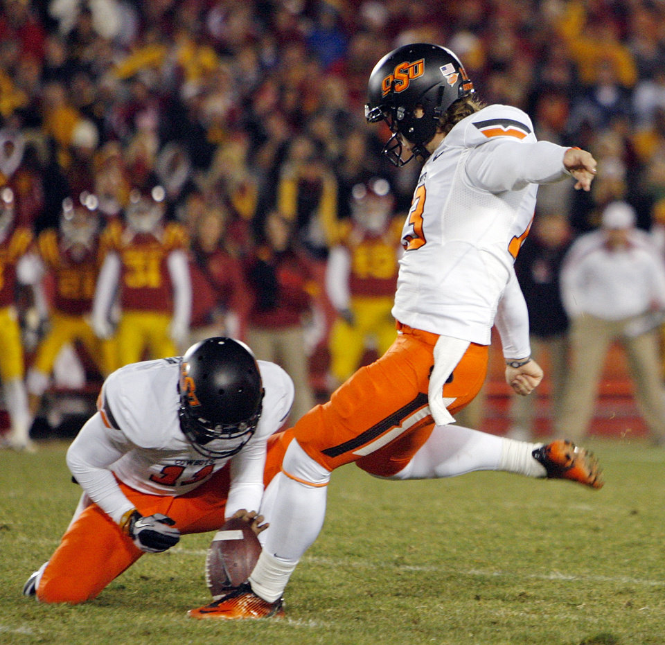 Photo - OSU's Quinn Sharp (13) attempts a field goal near the end of regulation as Wes Harlan (11) holds during a college football game between the Oklahoma State University Cowboys (OSU) and the Iowa State University Cyclones (ISU) at Jack Trice Stadium in Ames, Iowa, Friday, Nov. 18, 2011. Sharp missed the kick. Iowa State won, 37-31, in double overtime. Photo by Nate Billings, The Oklahoman