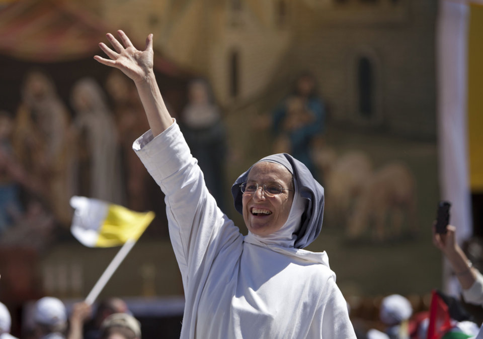 Photo - A nun waves to the helicopter carrying Pope Francis on his way to a mass in Manger Square next to the Church of the Nativity, traditionally believed to be the birthplace of Jesus Christ in the Palestinian West Bank city of Bethlehem, Sunday, May 25, 2014. Francis landed in Bethlehem, the cradle of Christianity, in a symbolic nod to Palestinian aspirations for their own state. He called the stalemate in peace talks