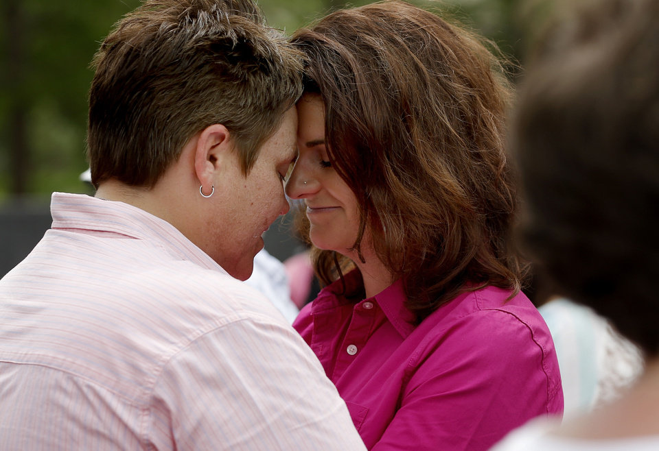 Photo - Cheri Bolz, left, and Kristen Perkins of Oklahoma City embrace during the The Love is Love marriage equality rally & commitment ceremony at the Myriad Botanical Gardens in Oklahoma City, Saturday, May 18, 2013. Cheri and Kristen have been together for eight years. Photo by Bryan Terry, The Oklahoman