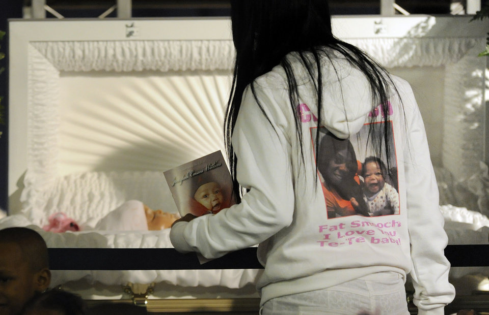 Photo - A mourner pays respect before the funeral for 6-month old Jonylah Watkins at New Beginnings Church in Chicago, Tuesday, March, 19, 2013. Jonylah was killed when a gunman fired at a minivan as she sat on her father's lap on March 11. Her death was the latest to draw national attention to Chicago's struggle with gang violence and murder.  (AP Photo/Paul Beaty)