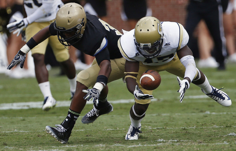 Photo - Georgia Tech defensive back Lance Austin (17) breaks up a pass intended for Wofford running back Octavius Harden (33) during the second half of an NCAA college football game, Saturday, Aug. 30, 2014, in Atlanta. Georgia Tech won 38-19. (AP Photo/Mike Stewart)