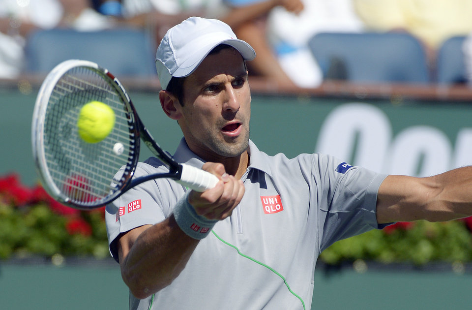 Photo - Novak Djokovic, of Serbia, hits a shot from Roger Federer, of Switzerland, in the final match of the BNP Paribas Open tennis tournament, Sunday, March 16, 2014, in Indian Wells, Calif. (AP Photo/Mark J. Terrill)