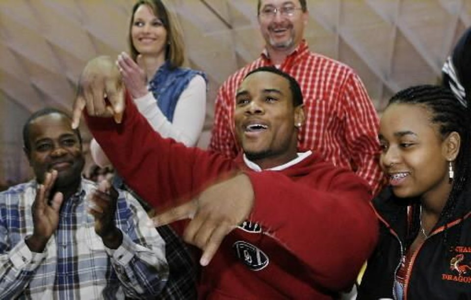 Dewar defensive back Ronnel Lewis flashes the upside down \'Horns gesture as he responds to loud applause from family, friends and student body who watched him sign letter of intent to play football at the University of Oklahoma during a school-wide assembly in the school\'s gym Wednesday morning, February 4, 2009. BY JIM BECKEL