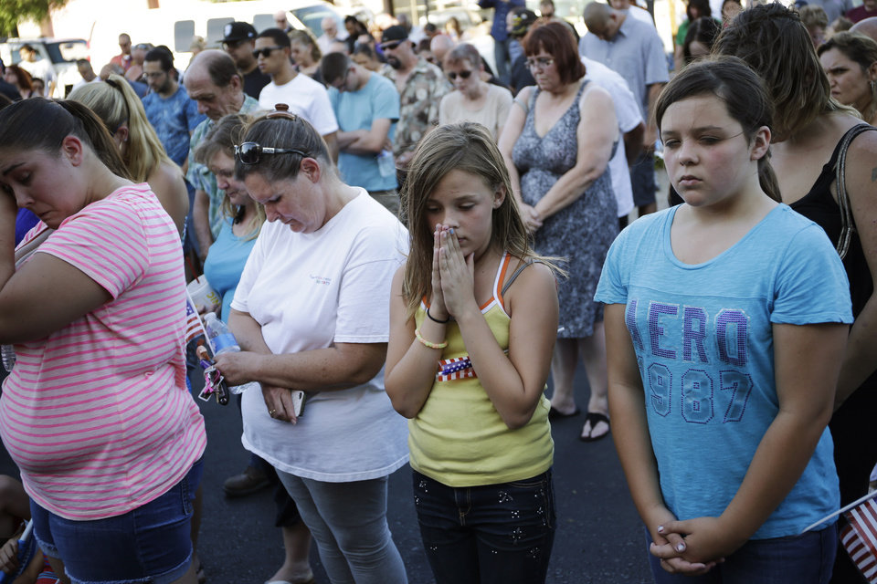 Photo - Alyssa Hernandez, center right, and Isabella Dominguez pray during a vigil near CiCi's Pizza Monday, June 9, 2014 in Las Vegas. The vigil was held to honor two Las Vegas Metropolitan Police officers and a bystander who were killed on Sunday. (AP Photo/John Locher)