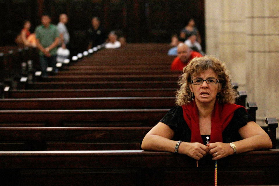 Photo - A woman recites the rosary at a local Catholic church where supporters of the ailing President Hugo Chavez gathered to pray for his health, in Caracas,Venezuela, Thursday, Dec. 13, 2012.  Venezuelans were warned that Chavez may not be well enough after his fourth cancer-related surgery in Cuba to be inaugurated on Jan. 10.  (AP Photo/Fernando Llano)