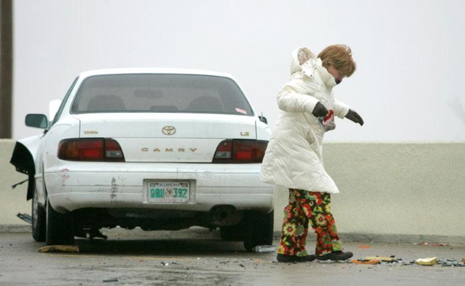 Photo -  Walking cautiously on an ice-covered Broadway Extension, an unidentified women tries to keep her balance after the car she was in was involved in a minor accident near Hefner Road in Oklahoma City, January  26, 2009.  BY STEVE GOOCH, THE  OKLAHOMAN