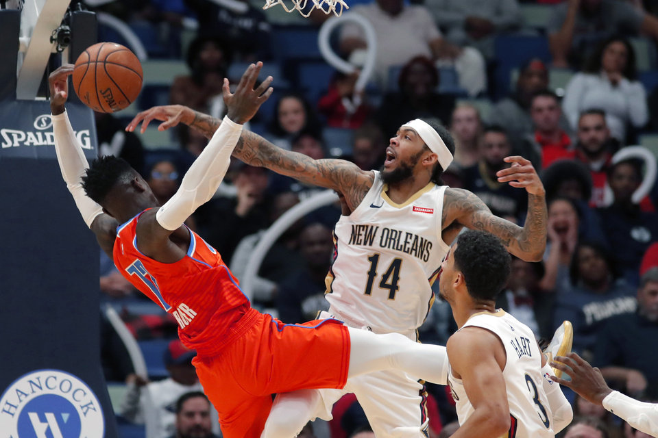 Photo - New Orleans Pelicans forward Brandon Ingram (14) blocks a shot by Oklahoma City Thunder guard Dennis Schroder in the second half of an NBA basketball game in New Orleans, Sunday, Dec. 1, 2019. (AP Photo/Gerald Herbert)