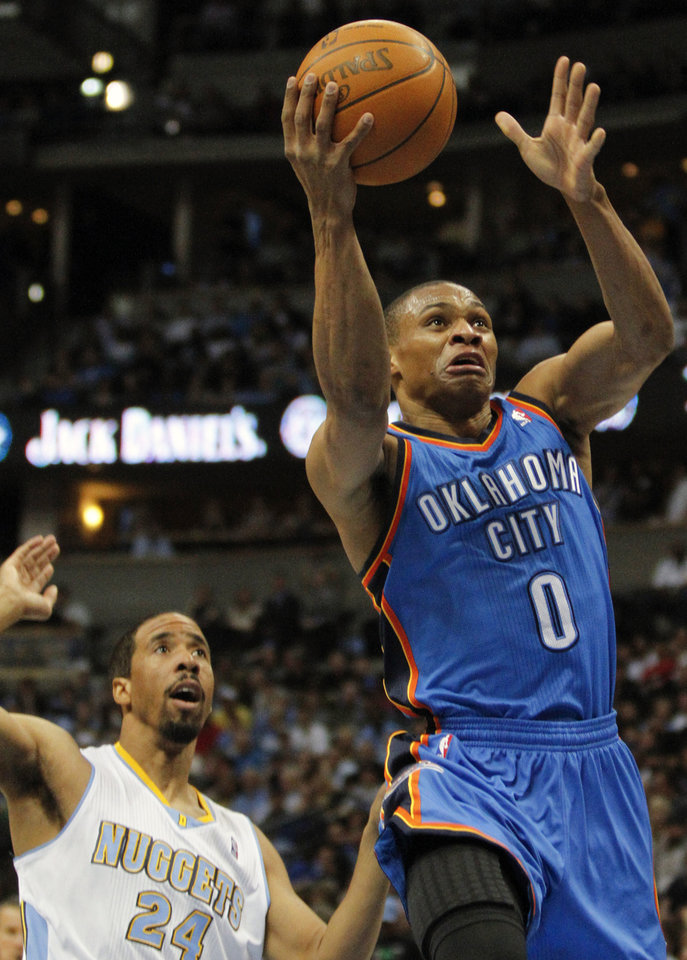 Oklahoma City Thunder guard Russell Westbrook (0) laysup past Denver Nuggets guard Andre Miller (24) during the first quarter of an NBA basketball game Thursday, March 15, 2012, in Denver. (AP Photo/Barry Gutierrez) ORG XMIT: COBG105