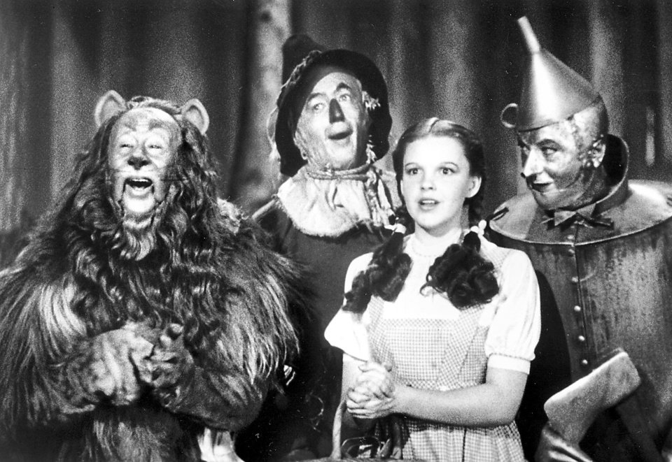 Photo - The Cowardly Lion (Bert Lahr), the Scarecrow (Ray Bolger), Dorothy (Judy Garland) and the Tin Woodman (Jack Haley) in the movie
