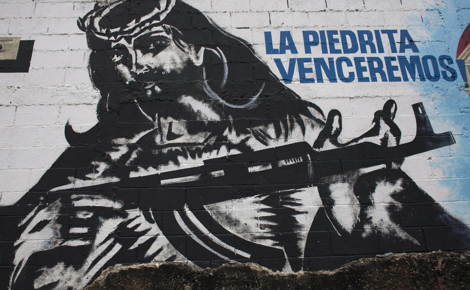 Photo -   In this Sept. 16, 2010 photo, a mural depicting an image of Jesus Christ holding a machine gun covers a wall in La Piedrita or Little Rock neighborhood gang turf in Caracas, Venezuela. Heavily armed gangs that pledge allegiance to President Hugo Chavez rule over fiefdoms in slums where police rarely patrol, employing vigilante justice and collecting extortion money. A shooting attack on the opposition candidate's entourage has kindled worries that Chavez's defenders could resort to violence if cancer impedes his bid for re-election. The gangs, however, are loosely organized and do not appear to be taking orders from the government. (AP Photo/Ariana Cubillos)
