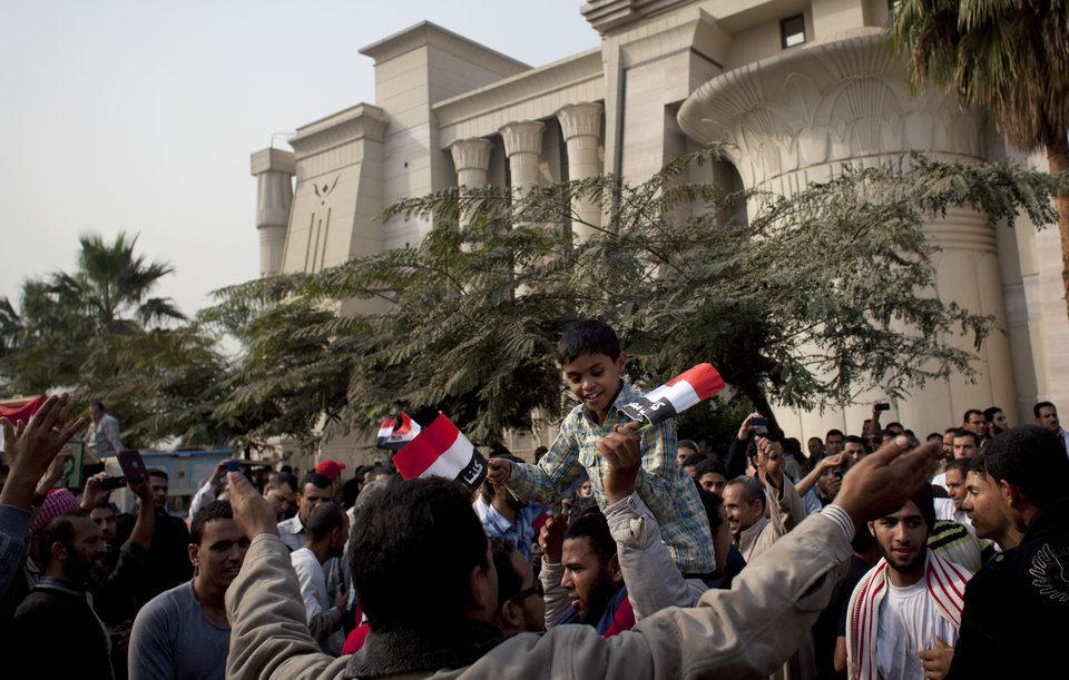 "Photo - Supporters of Egyptian President Mohammed Morsi chant slogans in front of Egypt's top court, background, in Cairo, Egypt, Sunday, Dec. 2, 2012. Egypt's top court announced on Sunday the suspension of its work indefinitely to protest ""psychological and physical pressures,"" saying its judges could not enter its Nile-side building because of the Islamist president's supporters gathered outside. (AP Photo/Nasser Nasser)"