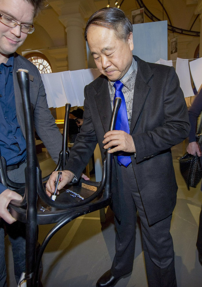 Photo - The 2012 Nobel Literature Prizewinner, Mo Yan of China, right, traditionally signs his chair at the Nobel Museum in Stockholm, Thursday Dec. 6, 2012. The chair signing is one of the traditions during the week leading up to the Nobel Prize ceremony that will take place in Stockholm on Dec. 10. (AP Photo/Fredrik Sandberg, Scanpix) SWEDEN OUT