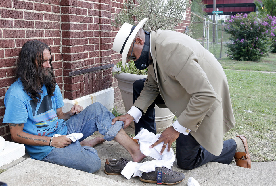 Photo -  The Rev. Robert Turner washes the feet of Ryan Barnes on July 22 outside  Tulsa's Vernon African Methodist Episcopal Church, where Turner is senior pastor.