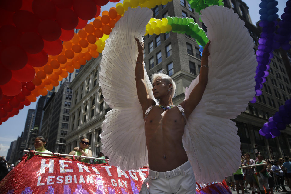 Photo - Kent Chua poses for pictures at the start of the Gay Pride Parade in New York, Sunday, June 29, 2014. Fifth Avenue became one big rainbow on Sunday, as thousands of participants waving multicolored flags made their way down the street for New York City's annual Gay Pride march. (AP Photo/Seth Wenig)