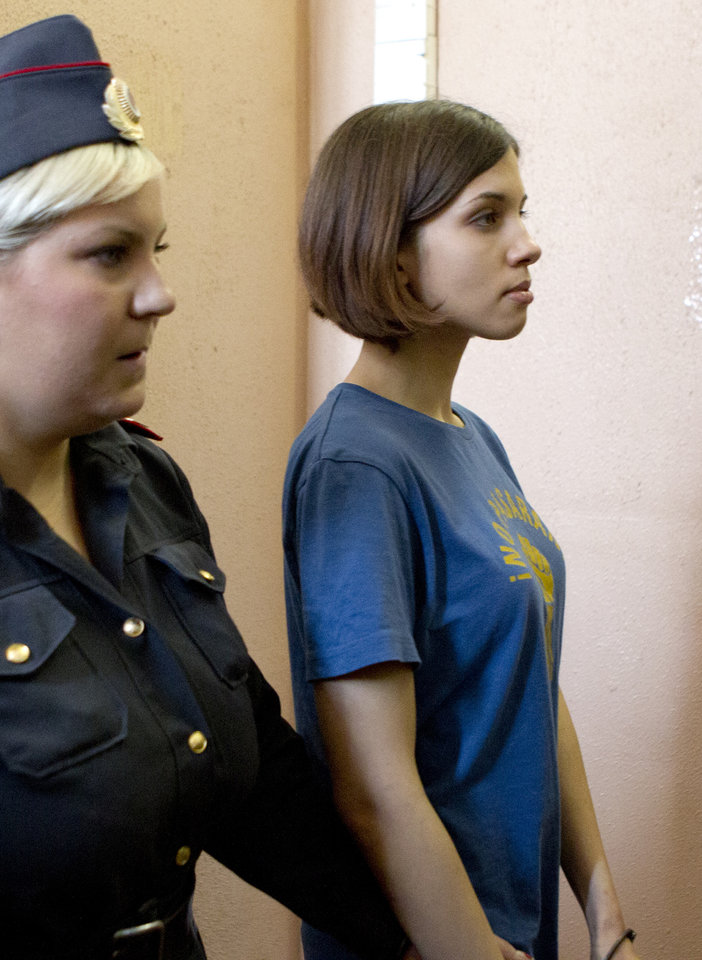 Photo -   Nadezhda Tolokonnikova, right, a member of feminist punk group Pussy Riot is escorted to a court room in Moscow, Russia, Friday, Aug. 17, 2012. Security is tight around the Moscow courthouse where three members of the feminist punk band Pussy Riot are to hear the verdict Friday in a trial that could send them to prison for seven years. (AP Photo/Misha Japaridze)